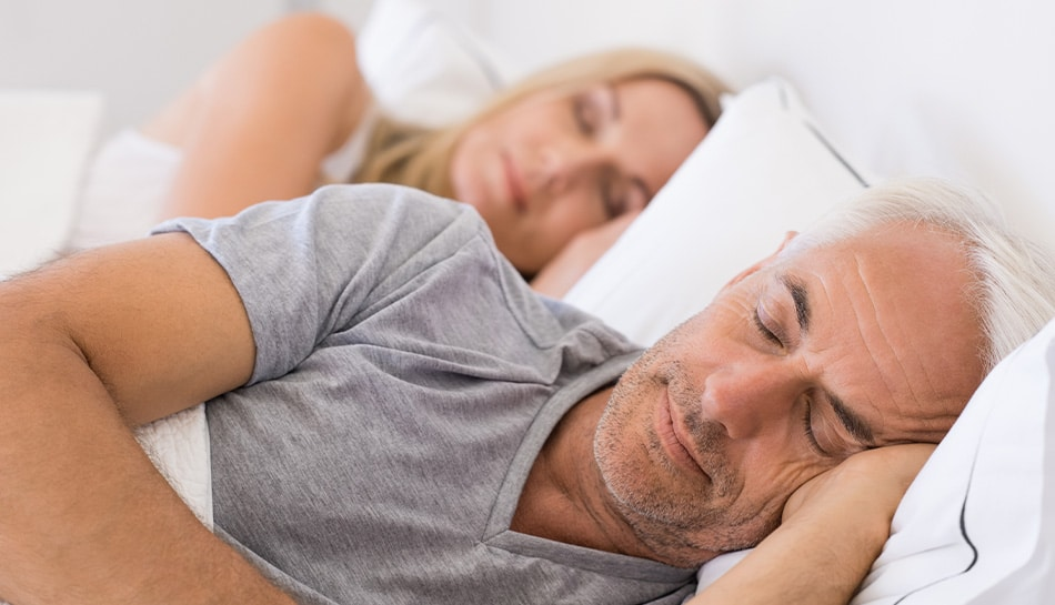 mature couple sleeping peacefully in bed together.