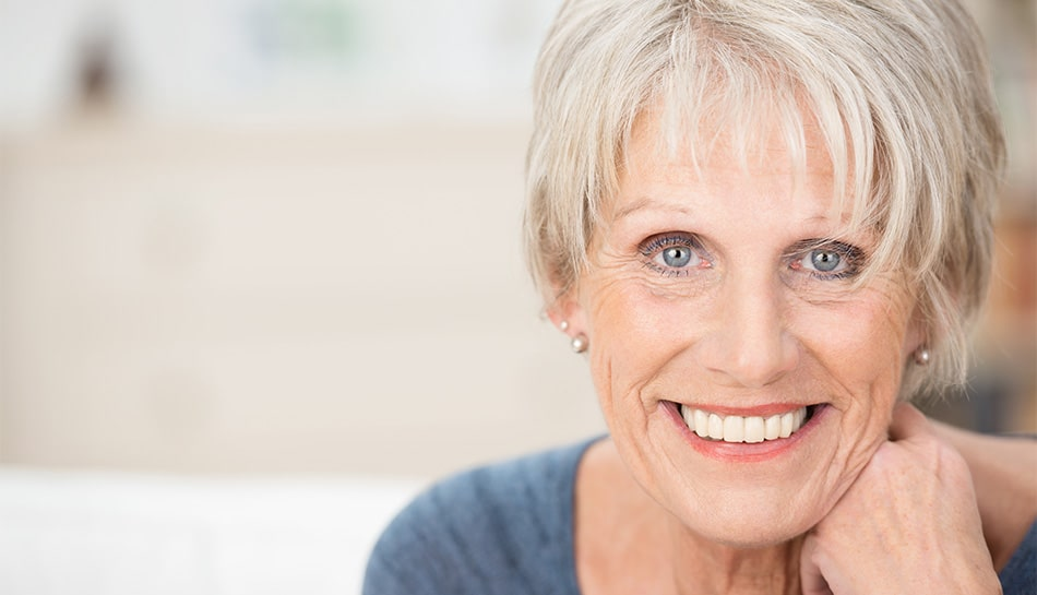 mature woman leaning on her hand, smiling