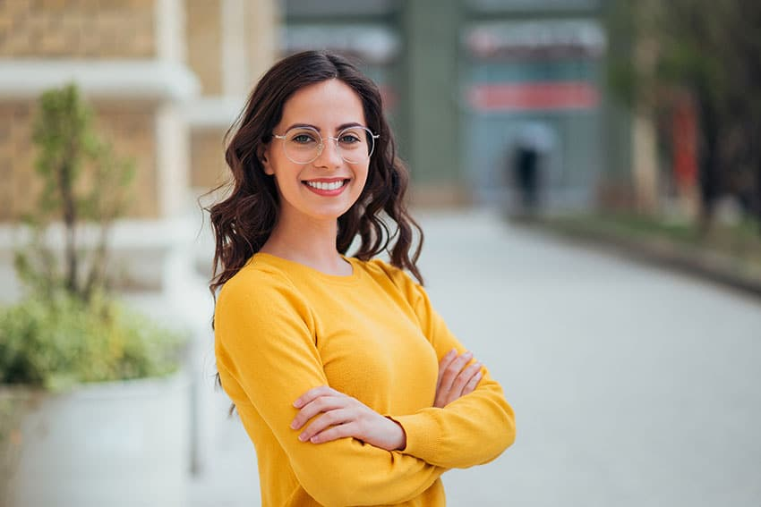 cute woman in yellow sweater crosses her arms and smiles